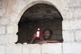 haiti-2010-man-looking-with-drink-out-of-ruin